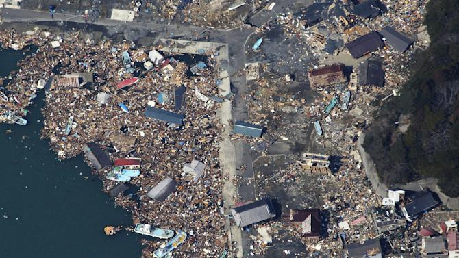 Debris covers part of a fishing port on Izushima island in Onagawacho, northern Japan, Monday, March 14, 2011, three days after a powerful earthquake-triggered tsunami hit the country's east coast. (AP Photo/The Yomiuri Shimbun, Atsushi Taketazu) JAPAN OUT, CREDIT MANDATORY