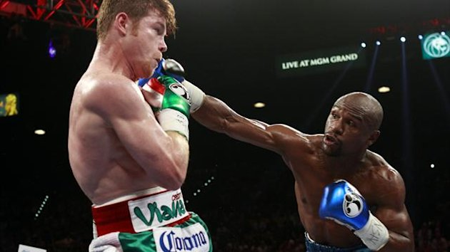 Canelo Alvarez (L) avoids a punch from Floyd Mayweather Jr