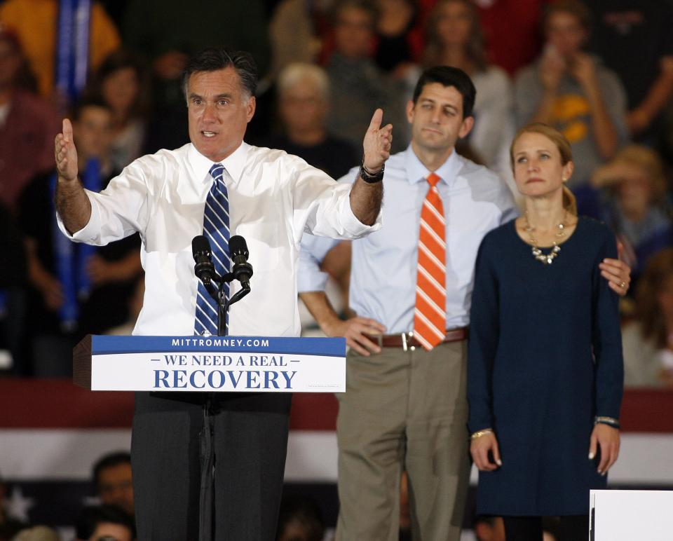 Republican presidential candidate former Massachusetts Gov. Mitt Romney speaks as running mate Rep. Paul Ryan, R-Wis., and his wife Janna listen during a campaign rally at the Marion County Fairgrounds in Marion, Ohio, Sunday, Oct. 28, 2012. (AP Photo/Mike Munden)