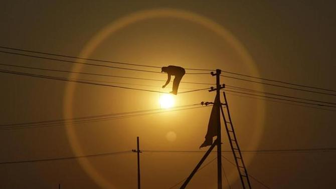 """An employee from the electricity board works on newly installed overhead power cables ahead of the """"Kumbh Mela"""", or Pitcher Festival, as the sun sets in Allahabad December 7, 2012. REUTERS/Jitendra Prakash/Files"""