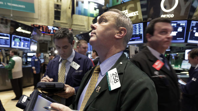 James Riley, center, works with fellow traders on the floor of the New York Stock Exchange Tuesday, Jan. 29, 2013. Stocks opened mixed on Wall Street, with the Standard & Poor's 500 holding at 1,500. (AP Photo/Richard Drew)