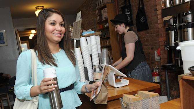 IMAGES DISTRIBUTED FOR THERMOS - New Yorker Nanda Khemraj receives her free fill of coffee on the inaugural National Fill Your Thermos Brand Bottle Day, Thursday, May 23, 2013, at Cafe Grumpy in New York. This event is being held in select cities and coffee shops throughout the nation hosted by the iconic Genuine Thermos Brand to kick off the holiday weekend.  (Photo by Diane Bondareff/Invision for Thermos/AP Images)