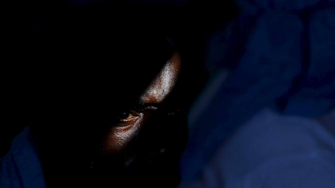 Sub-Saharan migrant sits on the deck of the Migrant Offshore Aid Station (MOAS) ship MV Phoenix in Vibo Valentia