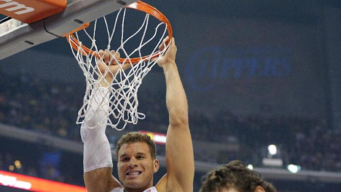 Los Angeles Clippers forward Blake Griffin, left, laughs along with Los Angeles Lakers forward Pau Gasol, of Spain, as he hangs on the rim after a play during the first half of their NBA basketball game, Sunday, April 7, 2013, in Los Angeles. (AP Photo/Mark J. Terrill)