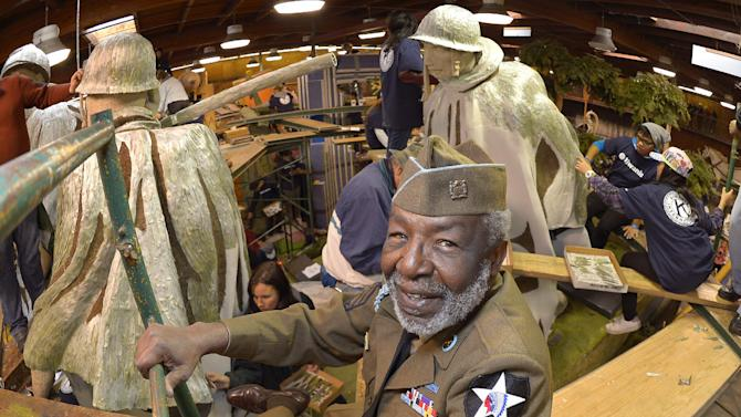 "Korean War veteran James McEachin, 82,  poses in front of the Rose Parade float ""Freedom Is Not Free"" by the Korean War Commemoration Committee, Saturday, Dec. 29, 2012, in Pasadena, Calif. McEachin is scheduled to ride the float in the Rose Parade on Tuesday, Jan. 1, 2013. (AP Photo/Mark J. Terrill)"