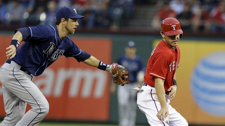 Tampa Bay Rays right fielder Ben Zobrist, left, tags Texas Rangers Ian Kinsler (5) on the run down between first and second base during the first inning of a baseball game Monday, April 8, 2013, in Arlington, Texas. Kinsler was caught trying steal second base. (AP Photo/LM Otero)