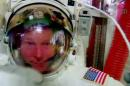 In this image made from video provided by NASA, astronaut Terry Virts points to his helmet as he sits inside the International Space Station on Wednesday, Feb. 25, 2015 during an inspection for water in his suit. Virts reported the water while he waited in the air lock for Wednesday's spacewalk to formally conclude. (AP Photo/NASA)