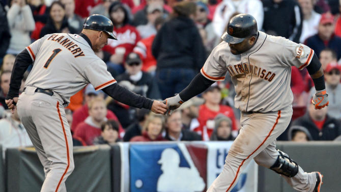 San Francisco Giants' Pablo Sandoval is congratulated by third base coach Tim Flannery (1) after hitting a two-run home run against the Cincinnati Reds in the seventh inning of Game 4 of the National League division baseball series, Wednesday, Oct. 10, 2012, in Cincinnati. (AP Photo/Michael Keating)