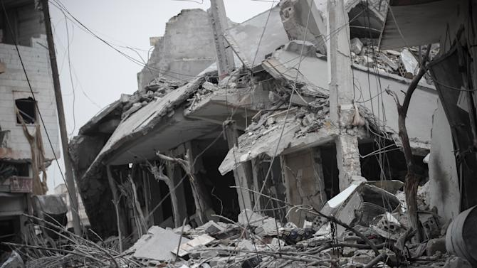 "In this Saturday Jan. 5, 2013 photo, damaged buildings are seen after heavy shelling by the Syrian Air Force in apparent retaliation for rebels attacks on the nearby Taftanaz military airbase in Binnish, Syria. Syrian President Bashar Assad, in a rare speech Sunday, outlined his own vision for ending the country's conflict with a plan that would keep him in power. He also dismissed any chance of dialogue with the armed opposition and called on Syrians to fight what he called ""murderous criminals."" (AP Photo/Mustafa Karali)"