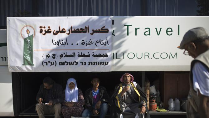 Activists sit in the trunk of a bus as they wait for a group of Palestinian children at the Erez border crossing
