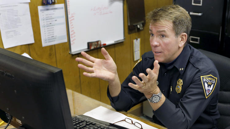 Steubenville police Chief William McCafferty sits behind a computer in his captains office as he tells how he gave the FBI an email that he had opened earlier which disabled his computer on Wednesday, Jan. 9, 2013, in Steubenville, Ohio. (AP Photo/Keith Srakocic)