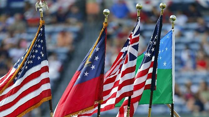 A Color Guard from the Sons of the Revolution marches off the field after the national anthem before a baseball game between the Atlanta Braves and the Philadelphia Phillies, Saturday, July 4, 2015, in Atlanta. (AP Photo/John Bazemore)