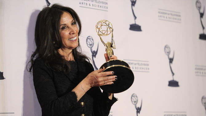 "Olivia Harrison poses backstage with the award for outstanding nonfiction special for ""George Harrison: Living in the Material World"" at the 2012 Creative Arts Emmys at the Nokia Theatre on Saturday, Sept. 15, 2012, in Los Angeles. (Photo by Chris Pizzello/Invision/AP)"