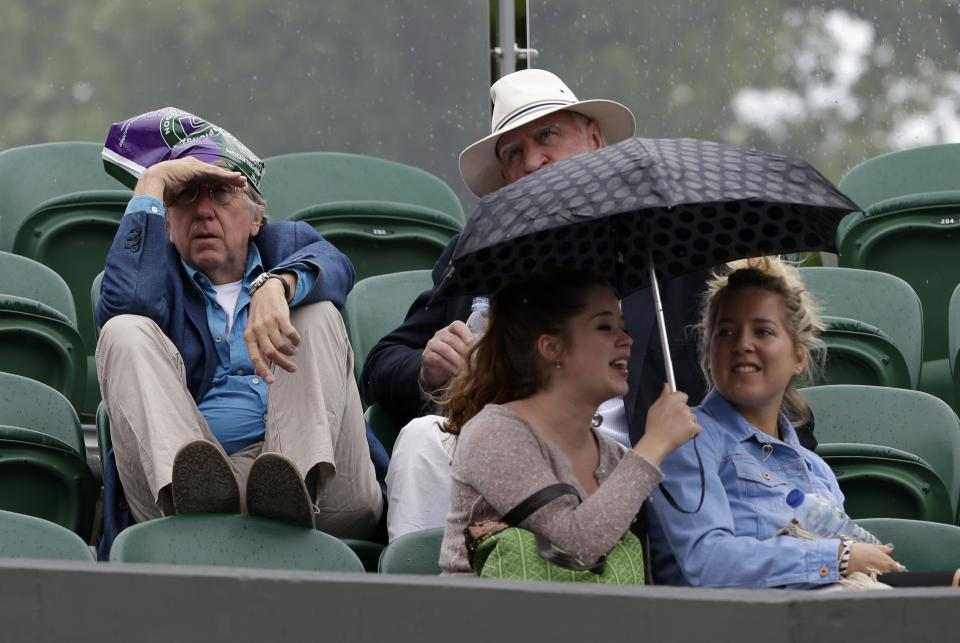 Spectators try to shield themselves from light rain as play is delayed at the All England Lawn Tennis Championships in Wimbledon, London, Thursday, June 27, 2013. (AP Photo/Anja Niedringhaus)