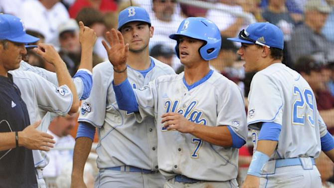 UCLA's Kevin Kramer (7) is greeted by teammates, including Ty Moore, right, after he scored against Mississippi State on a single by Pat Valaika in the first inning of Game 1 of the NCAA College World Series best-of-three finals, Monday, June 24, 2013, in Omaha, Neb. (AP Photo/Francis Gardler)