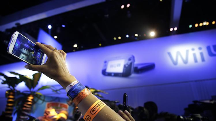 A show attendee uses her smartphone to record the remarks from Reggie Fils-Aime, President and chief operating officer of Nintendo of America, at the Nintendo Wii U software showcase during the E3 game show in Los Angeles, Tuesday, June 11, 2013. (AP Photo/Jae C. Hong)