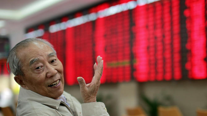 An investor gestures as he monitors the stock prices at a private securities company Thursday, Nov. 1, 2012 in Shanghai, China. Asian stock markets were mixed Thursday, with investors buoyed by solid manufacturing data out of China but wary of weak global demand for electronics after Panasonic Corp. forecast a massive loss. (AP Photo)