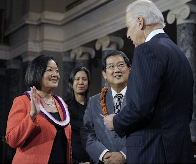 Vice President Joe Biden administers the Senate Oath to Sen. Mazie Keiko Hinoro, D-Hawaii, accompanied by her husband Leighton Kim Oshima, during a mock swearing in ceremony on Capitol Hill in Washing