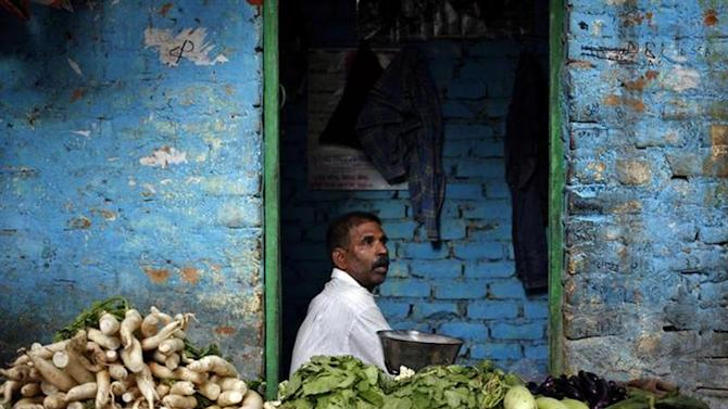 A vendor selling vegetables waits for customers at his stall inside a slum in New Delhi September 23, 2013. REUTERS/Anindito Mukherjee