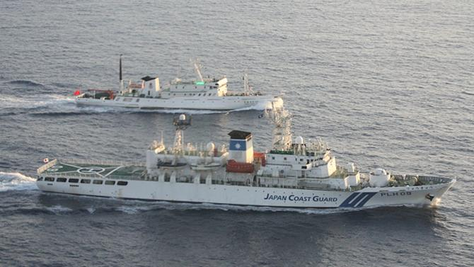 In this photo released by Japan Maritime Safety Agency, Japan Coast Guard patrol boat, foreground, sails by a Chinese vessel in waters off the disputed islands known as Senkaku in Japan and Diaoyu in China, in the East China Sea Wednesday, Aug. 24, 2011. Japan says it has protested to China after two Chinese patrol boats entered waters near islands in the East China Sea claimed by both countries. (AP Photo/Japan Maritime Safety Agency) EDITORIAL USE ONLY