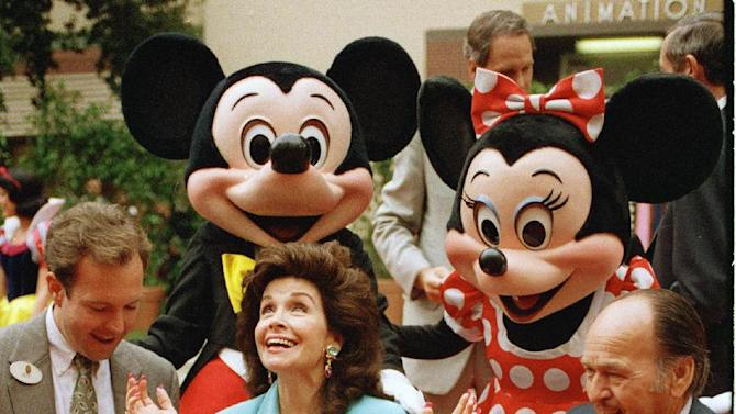 "FILE - In this Oct. 21, 1992 file photo, former ""Mouseketeer"" Annette Funicello gets set to put her hands in the cement at Walt Disney Studios Theatre, in Burbank, Calif., as she is honored with the Disney Legend Award. With Funicello is her husband, Glen Holt, right, and Jeff Hofman, left, Disney Studios official. Walt Disney Co. says, Monday, April 8, 2013, that Funicello, also known for her beach movies with Frankie Avalon, has died at age 70. (AP Photo/Nick Ut, File)"