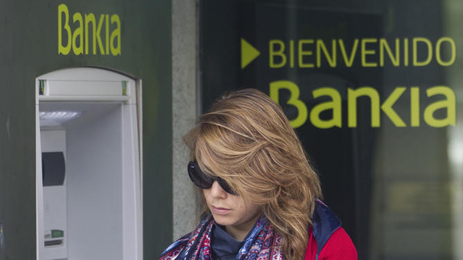 A woman uses an ATM cash point machine at a branch of the Bankia bank in Madrid Thursday May 17, 2012. A recently nationalized Spanish bank's shares plummeted Thursday after a newspaper said depositors were rushing to withdraw money, while the country paid sharply higher interest rates in a debt auction, reflecting concerns the country will be caught up in the fallout of the Greek crisis. Logo says ' Welcome to Bankia'. (AP Photo/Paul White)