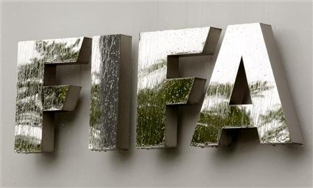 Water flows over the FIFA logo in front of the FIFA headquarters during heavy rainfall in Zurich