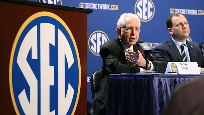 Southeastern Conference Commissioner Mike Slive, left, speaks while sitting next to SEC Network President Justin Connolly during a press conference the day before the SEC Football Championship game at the Georgia Dome, Friday, Dec. 6, 2013,  in Atlanta, Ga.,