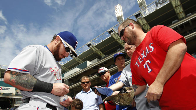 Texas Rangers' Josh Hamilton signs an autograph for a fan prior to the Rangers baseball game against the Cleveland Indians Monday, May 25, 2015, in Cleveland. (AP Photo/Aaron Josefczyk)