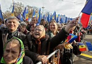People wave EU and Moldavian national flags, and shout…