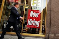 A man walks by a &quot;now hiring&quot; sign in the window of a fast food restaurant in New York City. Expectant eyes from around the world will be on Ben Bernanke Friday, looking for assurances that the US economy is solid or, if not, that his Federal Reserve is ready to invest more to stimulate growth
