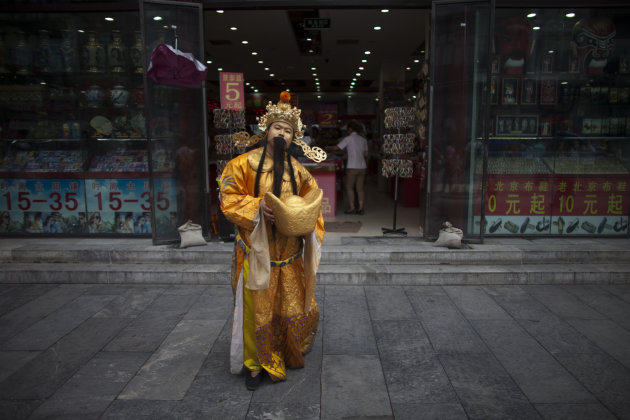 A souvenir shop employee dressed up as the Chinese God of Fortune holds a paper-made gold ingot in front of the shop to attract customers on a shopping street in central Beijing, China, Monday, July 9, 2012. China's inflation fell to a 29-month low in June, giving Beijing more room to fight a deepening economic slowdown. (AP Photo/Alexander F. Yuan)