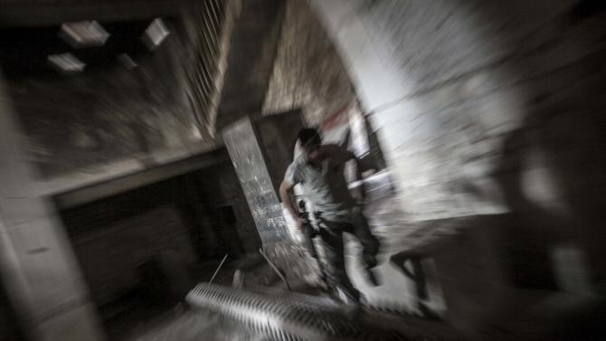 In this Monday, Oct. 29, 2012 photo, a rebel fighter belonging to the Qatebee Sokor Al-Islam group sneaks through a residential building as he looks for a firing position during clashes between rebel fighters and the Syrian army  in the Jedida district of Aleppo, Syria. Syrian fighter jets pounded rebel areas across the country on Monday with scores of airstrikes that anti-regime activists called the most widespread bombing in a single day since Syria's troubles started 19 months ago.(AP Photo/Narciso Contreras).