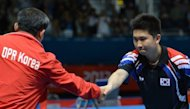 South Korea's Ryu Seung-Min (right) shakes hands with North Korea's coach after defeating Kim Hyok Bong of North Korea in a table tennis match at the Excel centre in London