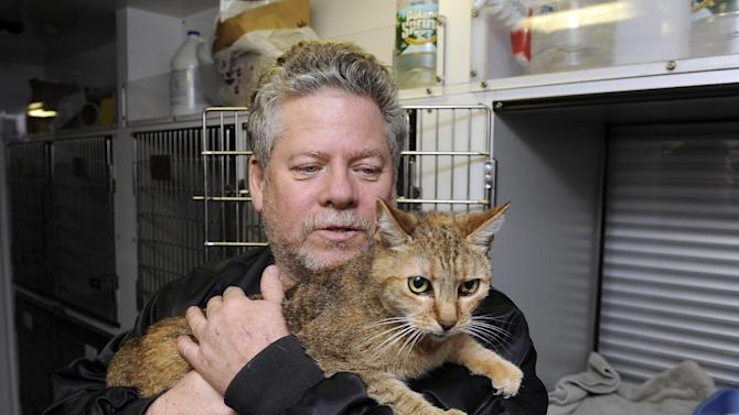 FILE - In this Oct., 28, 2012, file photo, Bill Ryan, of Inwood, N.Y., comforts his cat Amy before the arrival of Superstorm Sandy as he leaves his pet at shelter at Mitchell Park's Field House, run by the Nassau County Office of Emergency Management and Pet Safe Coalition in Uniondale, N.Y. Pet owners could drop of their pets at the shelter and afterwards seek shelter for themselves. (AP Photo/Kathy Kmonicek, File)