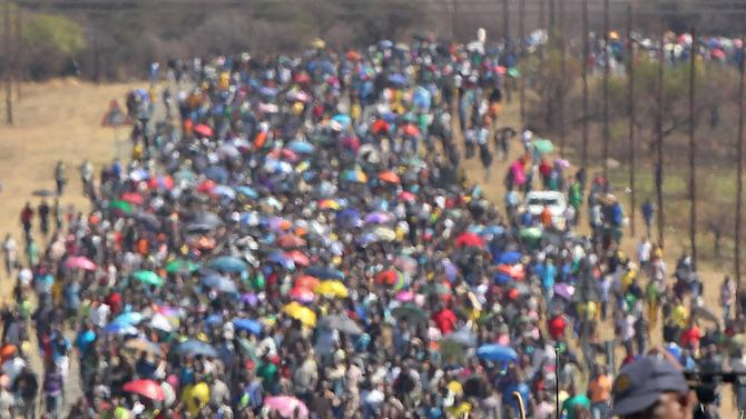 FILE In this photo taken Monday Sept. 10, 2012 miners march to Lonmin Platinum Mine near Rustenburg, South Africa in an attempt to stop operations. The current unrest in the mining industry started in August with the miners staging a wildcat strike that led to a violent confrontation in which police shot and killed 34. More than 70 others were wounded in the worst case of of state-led violence since the end of apartheid.  (AP Photo/Themba Hadebe-file)