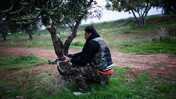 A Free Syrian Army fighter holds his weapon as he prepares himself for advance, close to a military base, near Azaz, Syria, Monday, Dec. 10, 2012. The gains by rebel forces came as the European Union denounced the Syrian conflict, which activists say has killed more than 40,000 people. (AP Photo/Manu Brabo)