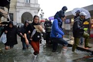 <p>People walk in a flooded street during a 'acqua alta' or high water on November 11, 2012 in Venice. The authorities have urged the local population to avoid going into the streets and to stay in the the upper floors of their homes.</p>