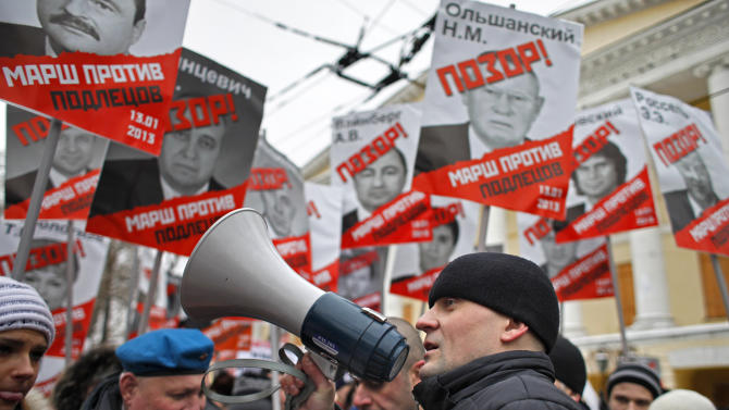 """Opposition leader Sergei Udaltsov, foreground, speaks during a protest rally in Moscow, Russia, Sunday, Jan. 13, 2013. Thousands of people are gathering in central Moscow for a protest against Russia's new law banning Americans from adopting Russian children. They carry posters of President Vladimir Putin and members of Russia's parliament who overwhelmingly voted for the law last month. The posters have the word """"Shame"""" written in red over the faces and proclaim that Sunday's demonstration is a """"March Against the Scum"""" who enacted the law.(AP Photo/Alexander Zemlianichenko)"""