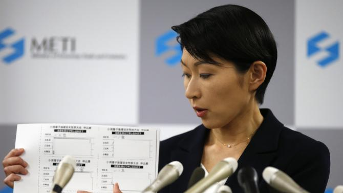 Japan's Economy, Trade and Industry Minister Obuchi, holding papers, speaks during a news conference at her ministry in Tokyo
