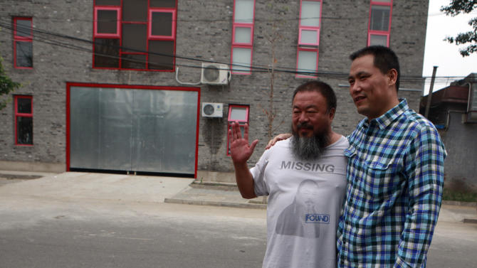 Dissident artist Ai Weiwei, left, poses with his lawyer Pu Zhiqiang before Pu leaves for the courthouse in Beijing, China, Friday, July 20, 2012. Chinese police on Friday barred Ai from attending the verdict on a lawsuit by his company against Beijing tax authorities. (AP Photo/Ng Han Guan)