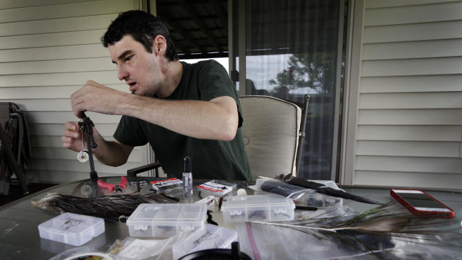 In this June 25, 2013 photo, Richard Norris ties a fishing fly at his home in Hillsville, Va. The man whose face was disfigured by a gunshot spent 15 years as a recluse, but now the 38-year-old is doing things he never would have before. (AP Photo/Chuck Burton)