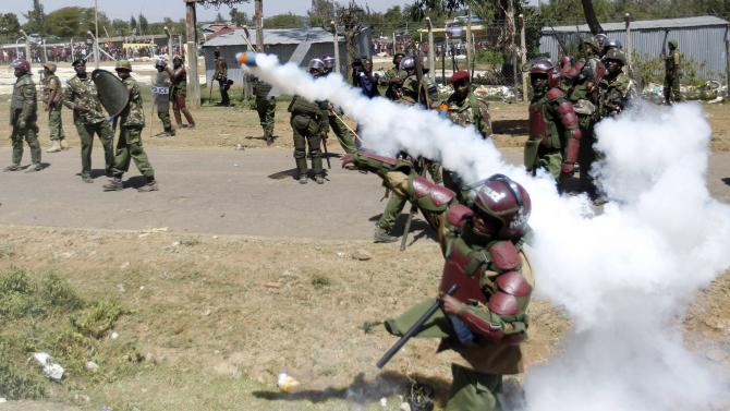 A riot policeman throws a teargas canister to disperse demonstrators during protests to oust Narok county Governor Samuel Tunai in Narok, Kenya