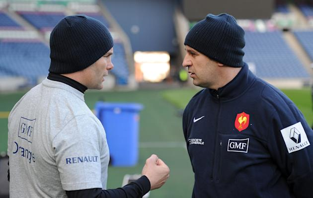 France's rugby union national team head coach Philippe Saint Andre (R) speaks with forward coach Yannick Bru during a training session on February 25, 2012 at Murrayfield Stadium in Edinburgh, on the