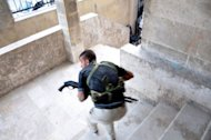 A Syrian rebel takes position during clashes with government troops at a police station in the Salhin district of the northern city of Aleppo