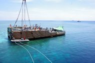 This undated handout photo released on March 30, 2013 by Philippine Coast Guard (PCG) shows the stern of the USS Guardian before being lifted by a boat crane during its salvage operation at Tubbataha reef, in Palawan island, western Philippines. The commanding officer and three crew have been relieved of their duties, the US Navy said Thursday