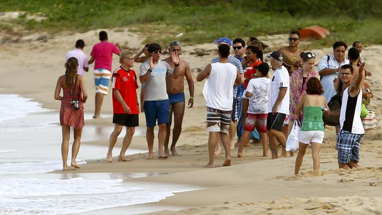 Germany's coach Joachim Loew speaks to people next to head match analyst Siegenthaler on the beach in front of their base camp Campo Bahia