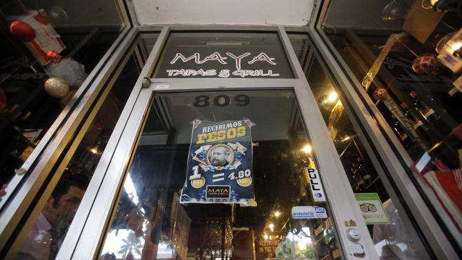 "A sign that reads, We Accept Pesos, is displayed at the main entrance of the Maya and Tapas Grill restaurant in Miami Beach, Fla., Thursday, Dec. 13, 2012. ""Eat in Miami, pay in pesos!"" the ad for the Maya Tapas & Grill restaurant proclaims. At the Maya restaurant along Miami Beach's famed Lincoln Road, clients can pay in Argentine pesos at the official exchange rate. (AP Photo/Alan Diaz)"