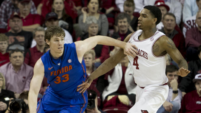 Florida's Erik Murphy (33) dribbles around Arkansas' Coty Clarke (4) during the first half an NCAA college basketball game in Fayetteville, Ark., Tuesday, Feb. 5, 2013. (AP Photo/Gareth Patterson)