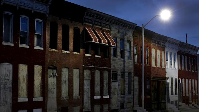 In this March 29, 2013 photo, vacant row houses line an empty street at dusk in Baltimore. The city has lost nearly a third of its population since it peaked in the 1950s, and today an estimated 16,000 buildings are vacant or abandoned. (AP Photo/Patrick Semansky)